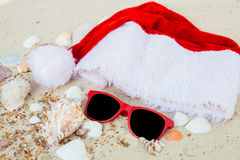 Christmas hat and red sunglasses on the beach. Santa   eyeglasses  the sand near shells. Holiday. New year vacation. Copy space. F Stock Images