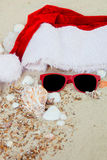 Christmas hat and red sunglasses on the beach. Santa   eyeglasses  the sand near shells. Holiday. New year vacation. Copy space. F Royalty Free Stock Photos