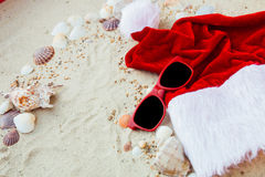 Christmas hat and red sunglasses on the beach. Santa   eyeglasses  the sand near shells. Holiday. New year vacation. Copy space. F Royalty Free Stock Photo