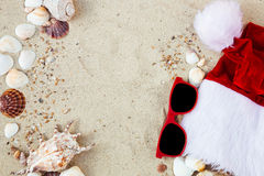 Christmas hat and red sunglasses on the beach. Santa   eyeglasses  the sand near shells. Holiday. New year vacation. Copy space. F Royalty Free Stock Images