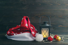 Christmas hat of Santa, Christmas lamp and glass spheres on a wooden background. Royalty Free Stock Photography