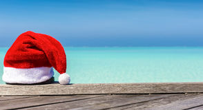 Christmas hat on wooden jetty on a tropical setting Stock Photo