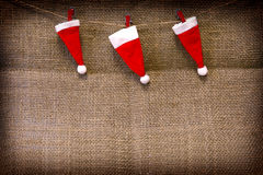 Christmas hats  hanging on brown cloth  background. Royalty Free Stock Photo