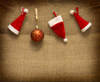 Christmas hats  hanging on brown cloth  background. Royalty Free Stock Photos
