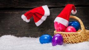 Christmas hats hanging, Easter eggs. Christmas hats hanging on a nail, Easter eggs Royalty Free Stock Photos
