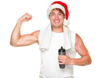 Christmas healthy exercise man showing muscles. Christmas fitness man showing bicep muscles fit for holidays. Handsome male in his 20s wearing santa hat isolated Royalty Free Stock Photo