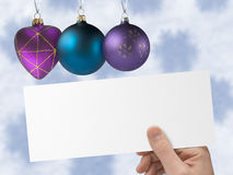 Christmas heart and balls, postcard in hand. Snowflakes on background Royalty Free Stock Photos