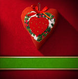 Christmas Heart Decoration on Red Velvet. Christmas heart hanging on red velvet background with ornate floral seamless and green plaque Stock Photography