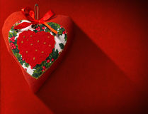 Christmas Heart Decoration on Red Velvet. Christmas heart, red, white and green hanging on red velvet background with shadows Royalty Free Stock Photos