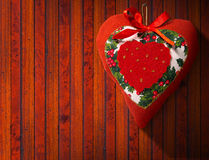 Christmas Heart Decoration on Wooden Wall. Christmas heart, red, white and green hanging on brown wooden wall with shadows Stock Photography