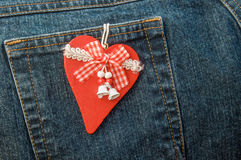 Christmas heart hanging on back pocket of jeans. Royalty Free Stock Photo