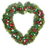 Christmas Heart Shaped Wreath. Decoration with red, green and silver bauble decorations, mistletoe, fir, blue spruce, cedar, pine cones and ivy leaves on white Stock Images