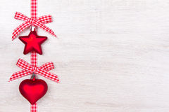 Christmas heart star bows red. Red Christmas tree decorations star and heart with checkered ribbon and bows on light wood, copyspace Stock Photo