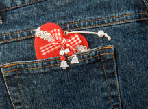 Christmas heart tucked into denim trouser pocket. Royalty Free Stock Photography