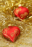 Christmas - Hearts. A red piece of Christmas decoration shaped as a heart lying in golden and silver lametta strings with another heart in the background (blury Royalty Free Stock Image