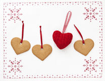 Christmas hearts. Gingerbread cookies with red ribbons and one knitted heart. Placed on table-cloth with ornaments Stock Photography