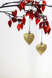 Christmas hearts. Two golden Christmas heart ornaments hanging from twig of red leaves. White background. Space for copy Stock Photo
