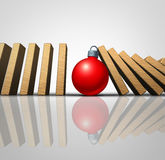 Christmas Help. And winter holiday support concept as falling domino pieces stopped by a supportive seasonal tree ornament as a volunteering metaphor for Royalty Free Stock Image