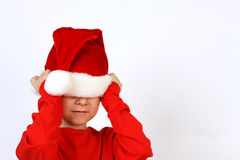 Christmas helper child put on Santas Claus hat on head front of white background Royalty Free Stock Images