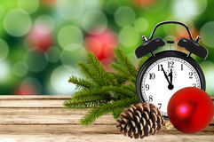 Christmas holiday background with alarm clock and tree branch on Stock Images