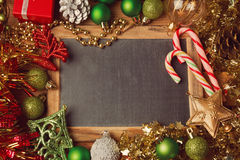 Christmas holiday background with blank chalkboard and Christmas decorations. Border design with copy space in the middle. Top..