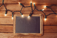Christmas holiday background with blank chalkboard and Christmas lights Stock Image
