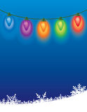 Christmas Holiday Background. Colored Christmas lights, with a blue background and snow drift background royalty free stock photo