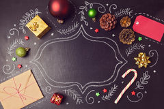 Christmas holiday background with decorations and hand drawings on chalkboard. View from above Royalty Free Stock Photo