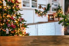 Christmas holiday background with empty rustic table and the bokeh of the living room with the Christmas tree on the second plan