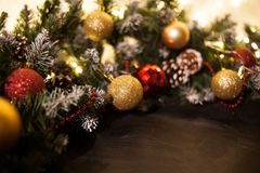 Christmas holiday background. Gifts with a red ribbon, Santa`s cap and decor under a Christmas tree on a wooden board. Close up. stock images