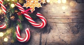 Christmas holiday background with gingerbread cookies, candy cane and evergreens border Royalty Free Stock Photo