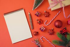 Christmas holiday background with notebook and decorations on red table. stock photography