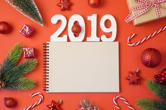 Christmas holiday background with notebook, 2019 new year and de. Corations on red table. Top view from above royalty free stock photo