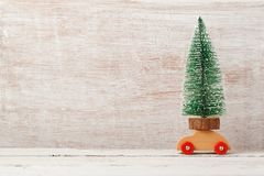 Christmas holiday background with pine tree on toy car. On wooden table royalty free stock images