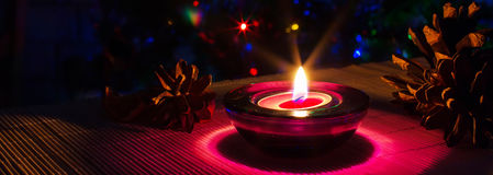 Christmas holiday background with purple candle and colorful lights with copyspace Royalty Free Stock Photos