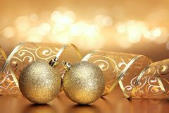 Christmas or holiday background with two golden ornaments. Ribbon and bokeh Stock Image