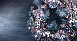 Christmas holiday background. Xmas wreath with spruce, cones and lights. Christmas decoration border over wooden table. Tabletop. Flatlay royalty free stock photography