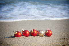 Christmas holiday / Baubles on the tropical beach. Christmas holiday / Red and Gold Baubles on the tropical beach Royalty Free Stock Image