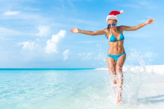 Christmas holiday beach fun bikini woman freedom. Christmas holiday beach fun vacation bikini woman running carefree splashing water enjoying freedom swim stock images
