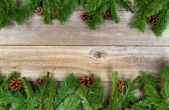 Christmas holiday border with evergreen branches on rustic cedar Stock Images