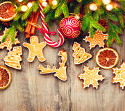Christmas holiday border with gingerbread cookies, candy cane over wood Royalty Free Stock Photo