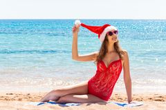 Christmas holiday on the coast. A girl in a red swimsuit and Santa Claus hat sits on a sandy beach, relaxed on a paradise rest.  stock image