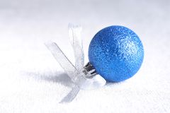 Christmas or holiday composition with blue silver balls on billowy feathers with snow and snowflakes. stock image