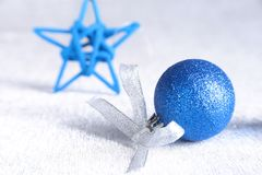 Christmas or holiday composition with blue silver balls on billowy feathers with snow and snowflakes. Christmas or holiday composition with blue silver balls on royalty free stock image