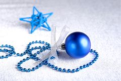 Christmas or holiday composition with blue silver balls on billowy feathers with snow and snowflakes. stock photo