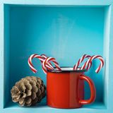 Christmas holiday composition with coffee cup, candy cane and pi. Ne corn on wooden shelf stock images