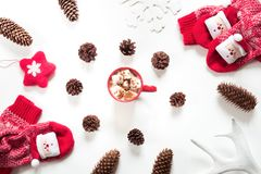 Christmas hot chocolate with marshmallow, cone, white fur, red felt star, knitted socks on white background. Christmas holiday composition. Hot chocolate with Stock Images