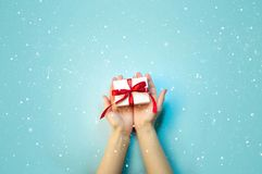 Christmas Holiday Composition. New Year Gift in White Box with Red Ribbon in Female Hands on Light Blue Background Flat Lay Top Vi royalty free stock photos