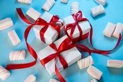 Christmas Holiday Composition. New Year Gift White Boxes Red Ribbon with Marshmallows on Blue Background. Flat Lay royalty free stock images