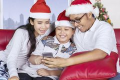Asian family with smartphone at Christmas time Royalty Free Stock Photos
